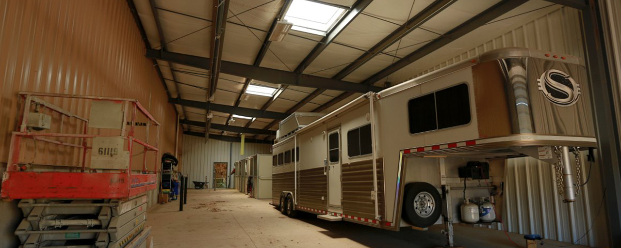 parked horse trailer and stables on side of horse arena facility